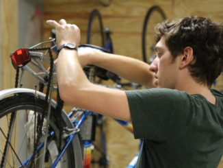 Vice-President Max Amar-Olkus '19 examines a shop bicycle brought back by a student with a broken chain.